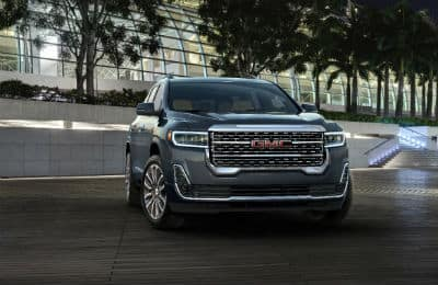 2020 GMC Acadia Denali exterior front fascia and passenger side parked in front of building