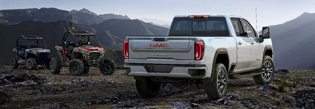 2020 GMC Sierra AT4 exterior back fascia and passenger side on hill with ATVs next to it