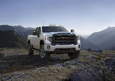 2020 GMC Sierra AT4 exterior front fascia and passenger side on hill with mountains in distance