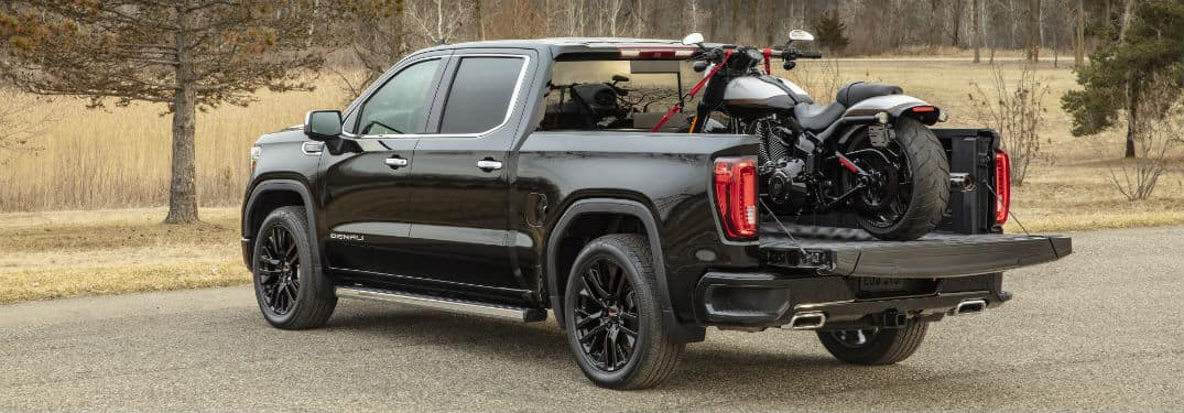 2020 GMC Sierra Denali exterior back fascia and driver side with dirt bike in bed