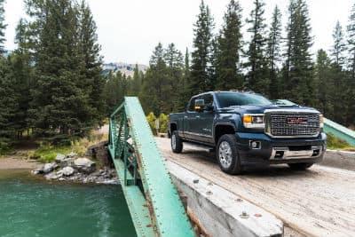 2019-GMC-Sierra-Denali-2500HD-exterior front fascia and passenger side going over wooden bridge