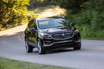 2020 Buick Enclave eterior front fascia and passenger side going fast on winding road with trees