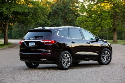 2020 Buick Enclave exterior back fascia and passenger side in empty lot with trees