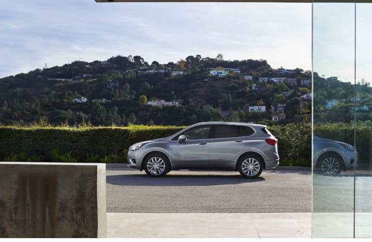 2020 Buick Envision exterior driver side profile in empty lot with hill in distance