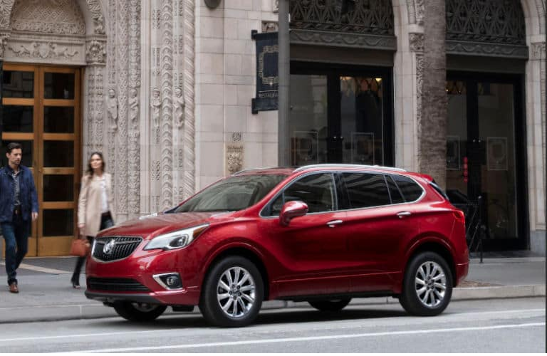 2020 Envision exterior front fascia and driver side in front of building with 2 people