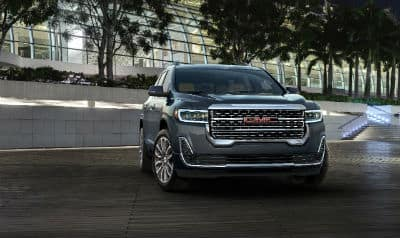 2020 GMC Acadia Denali exterior front fascia and passenger side in front of brick wall with trees