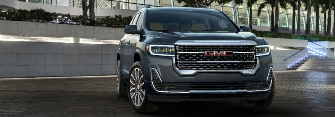 2020 GMC Acadia Denali exterior front fasica and passenger side in front of brick wall