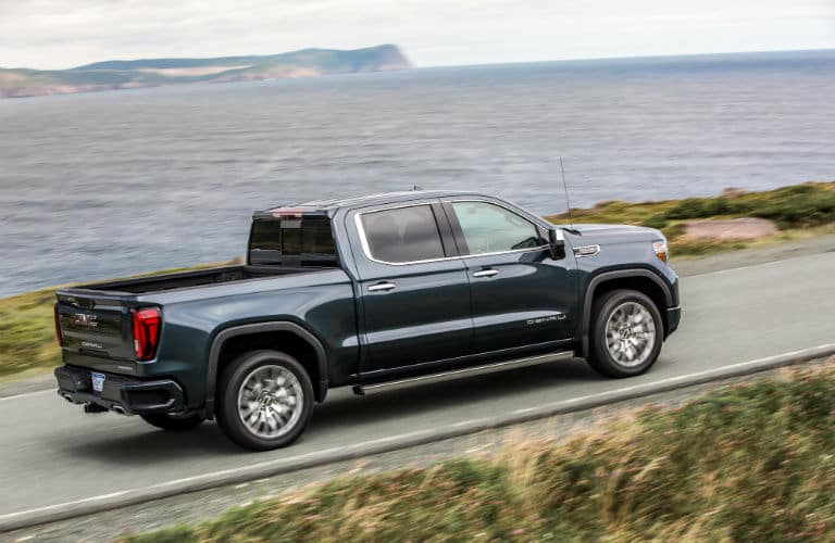 2020-GMC-Sierra-Denali exterior back fascia and passenger side going fast on ocean side road
