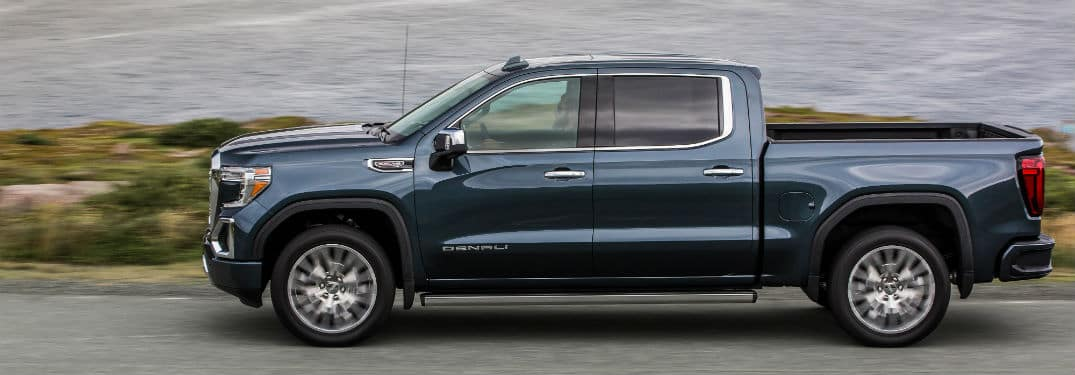 2020 GMC Sierra Denali exterior driver side profile on highway next to dark choppy lake