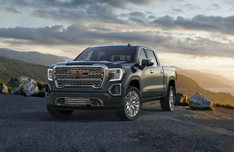 2020-GMC-Sierra-Denali exterior front fascia and driver side on hill with mountains in distance