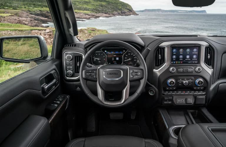 2020-GMC-Sierra-Denali interior front cabin steering wheel and display screen with ocean in window