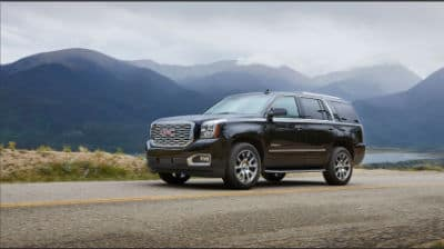 2020 GMC Yukon exterior front fascia and driver side on road with mountain background