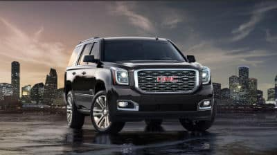 2020 GMC Yukon exterior front fascia and passenger side in front of city