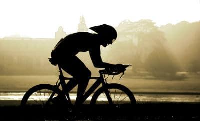 Silhouette of person biking in morning fog