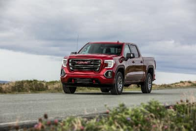 2020 GMC Sierra AT4 exterior front fascia and driver side on country road with cloudy sky