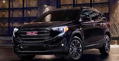 2020 GMC Terrain exterior front fascia and driver side in front of glass window at night