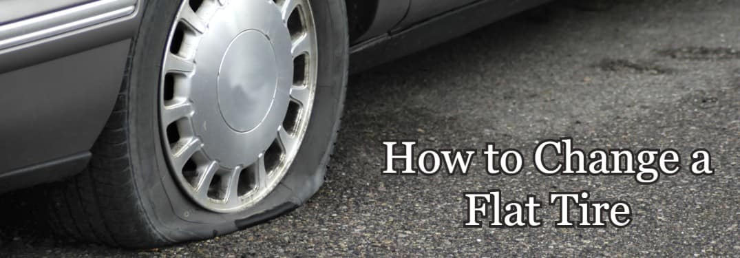 """Close up of a flat tire on a car with the text """"How to change a flat tire"""""""