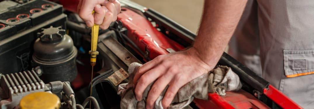 Mechanic using the dipstick to check the oil in a car engine