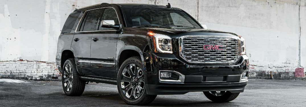 2019 GMC Yukon Denali exterior front fascia and passenger side in front of white wall