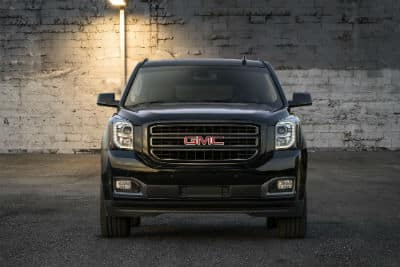 2019 GMC Yukon exterior front fascia in front of brick wall and lamp post