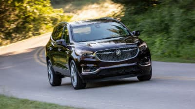 2020 Buick Enclave Avenir exterior front fascia and passenger side on winding road