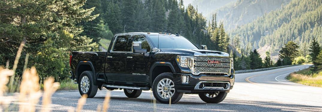 2020 GMC Sierra Denali exterior front fascia and passenger side on road with pine trees