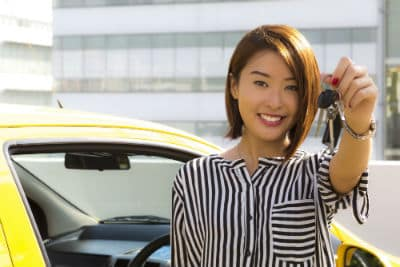 Woman holding up key in front of yellow car