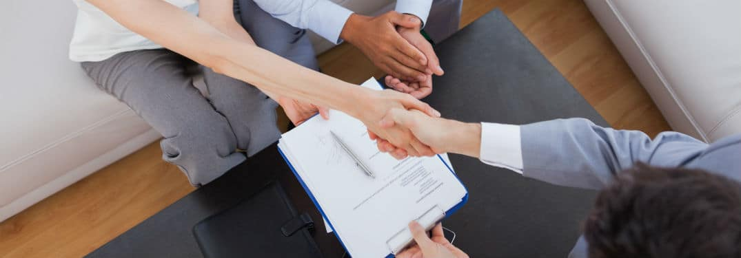 salesperson shaking hands with couple over paperwork