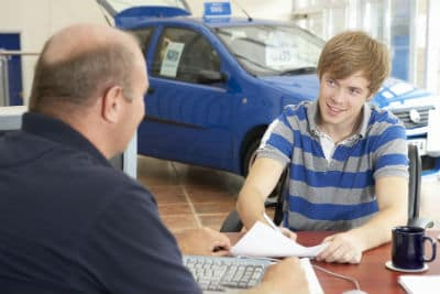 young man filling out paperwork at car dealership with salesman