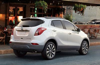 2020-Buick-Encore exterior back fascia and passenger side on side of road next to restaurant