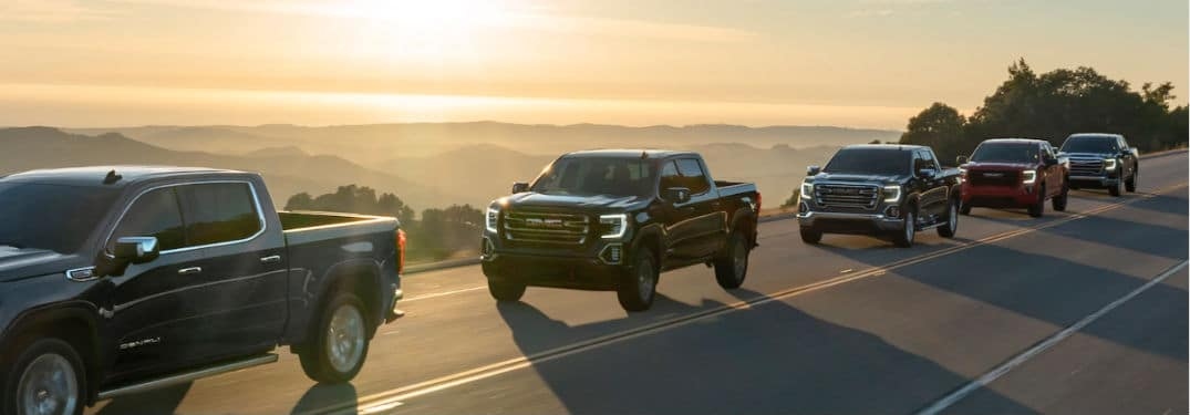 2020 GMC Sierra lineup exteriors front fascia and driver side on highway overlooking mountains