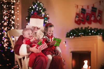 kids sitting on Santa lap in rocking chair in front of tree and fireplace