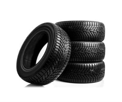 stack of three tires with tire leaning on left side of stack