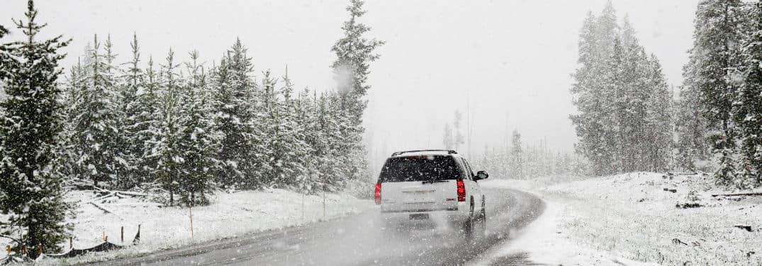 white SUV driving on tree lined highway with snow on ground and falling