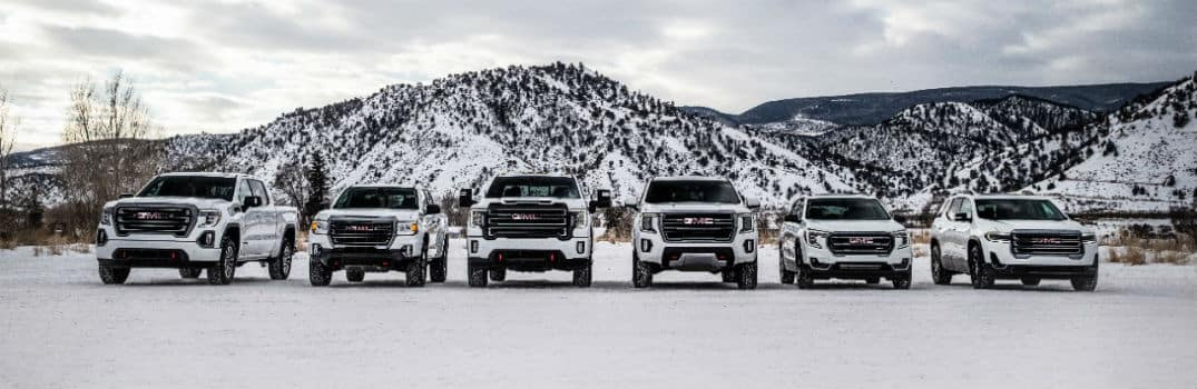 2021 GMC AT4 Lineup of Vehicles in front of snowy mountain