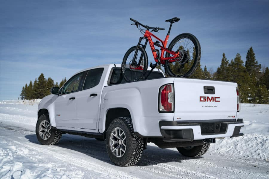 2021 GMC Canyon AT4 Exterior Driver Side Rear Profile with Bike in Snow