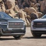 Two GMC Acadia parked next to each other before a mountainous background