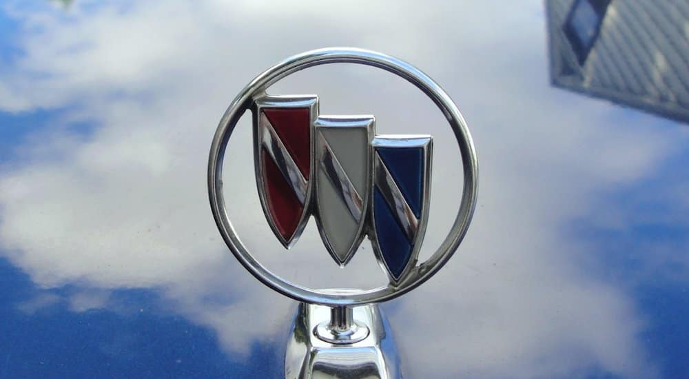 Closeup of the Buick 3 shield logo on a hood of a blue car