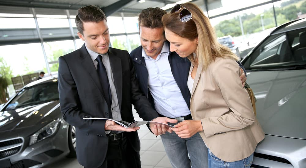 Couple in chevy dealership looking at brochure with salesman