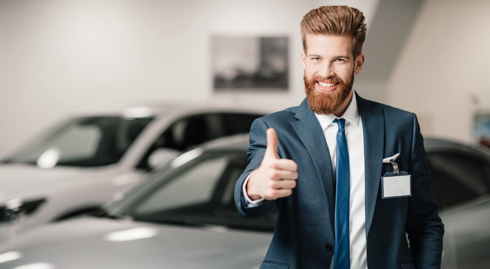 Bearded red headed car salesmen with thumb up