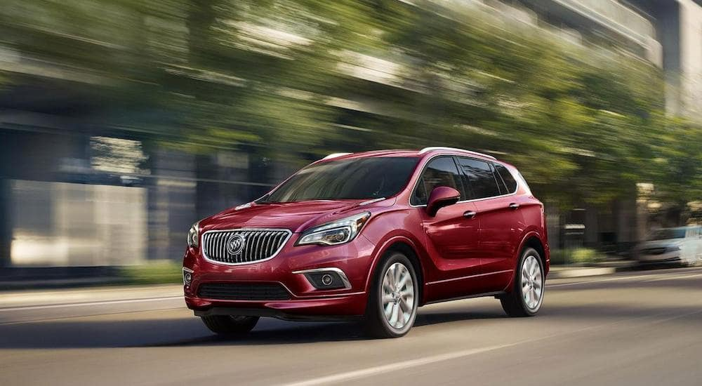 Red 2018 Buick Envision drives down a city street
