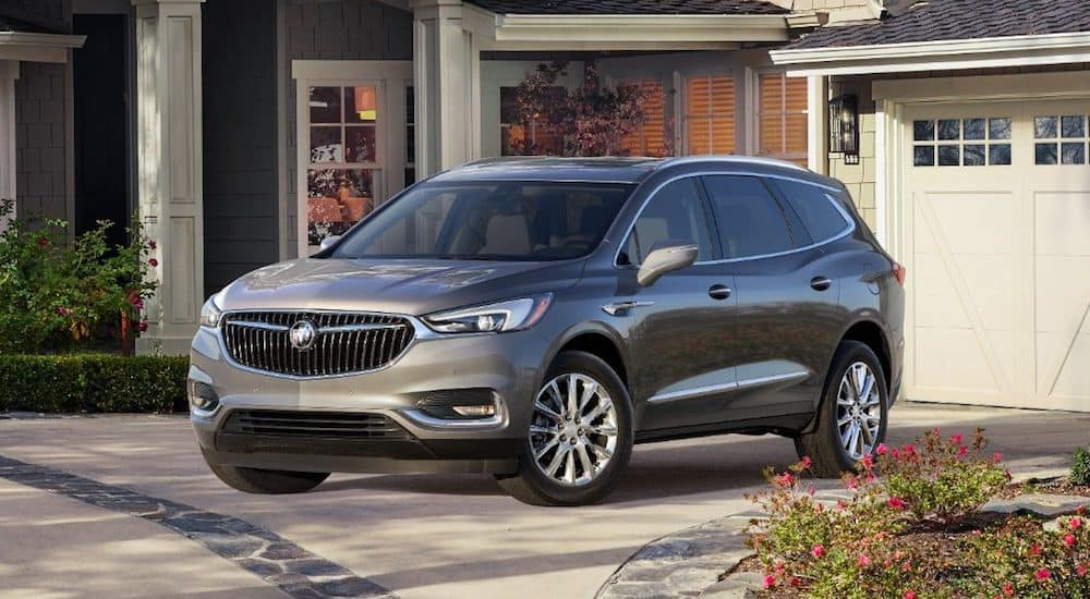 A silver 2019 Buick Enclave parked outside an upscale home