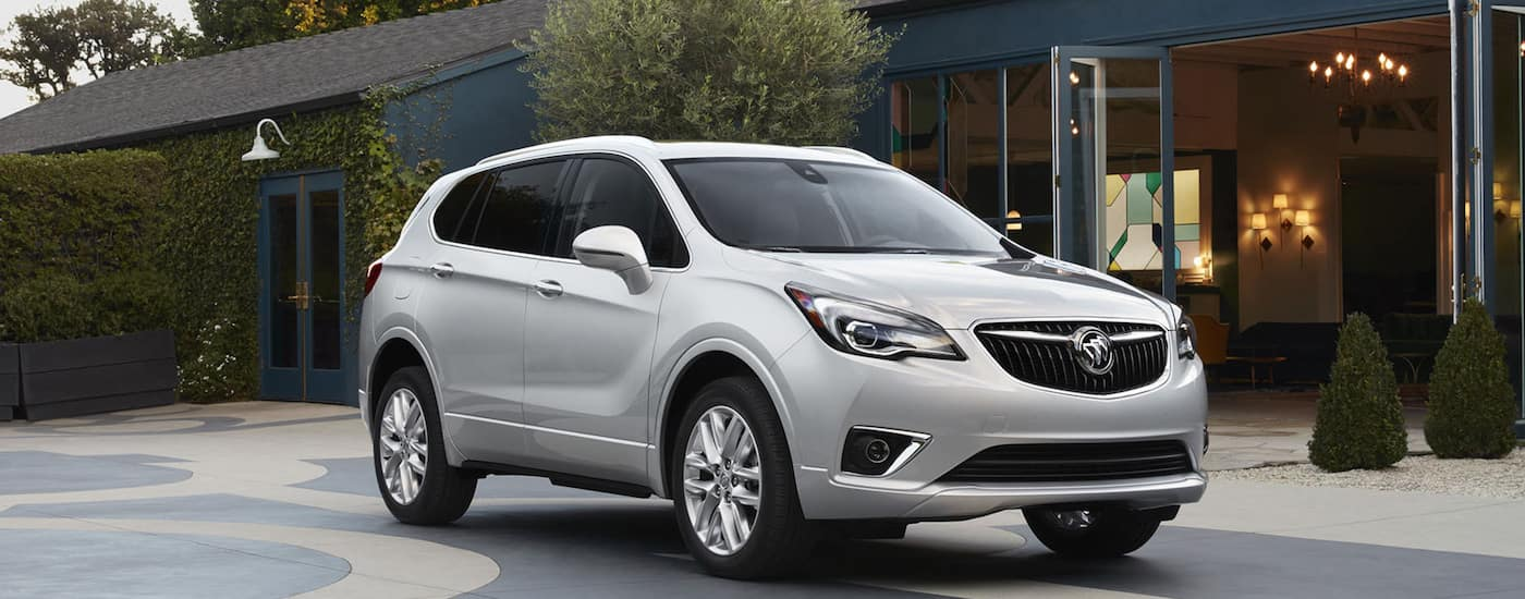 A silver 2019 Buick SUV parked outside a modern home
