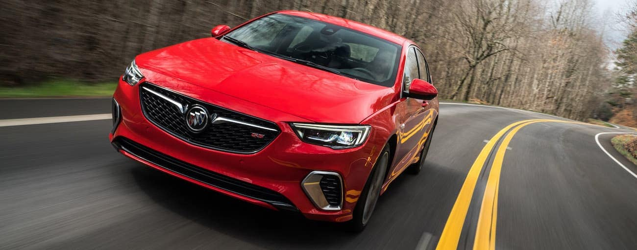 A red 2019 Buick Regal GS driving on a woodland road