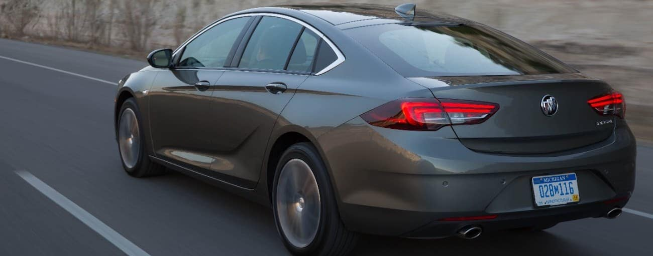 A gray 2019 Buick Regal driving by a stone wall
