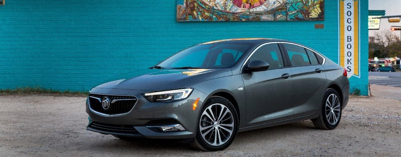 A gray 2019 Buick Regal in front of a teal book store