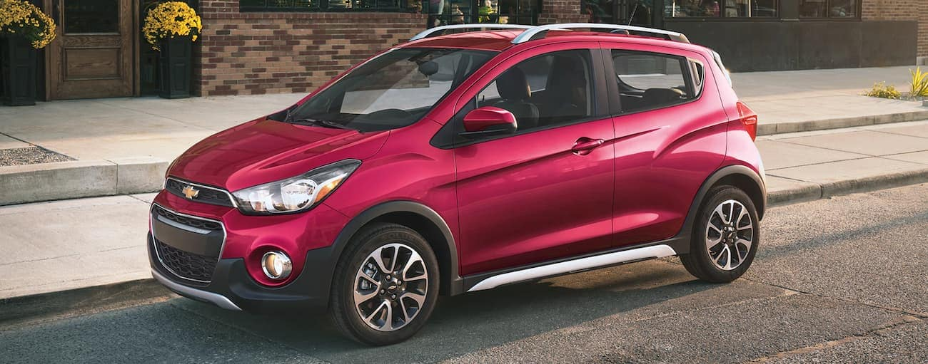 A red 2019 Chevy Spark ACTIV parked on a city street