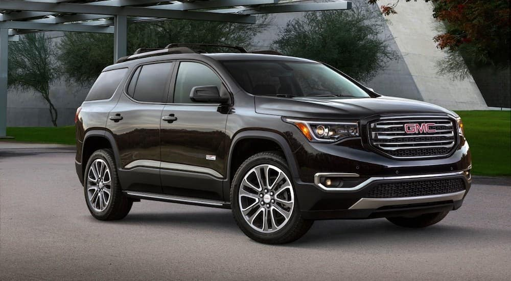 A black 2019 GMC Acadia in front of a modern building