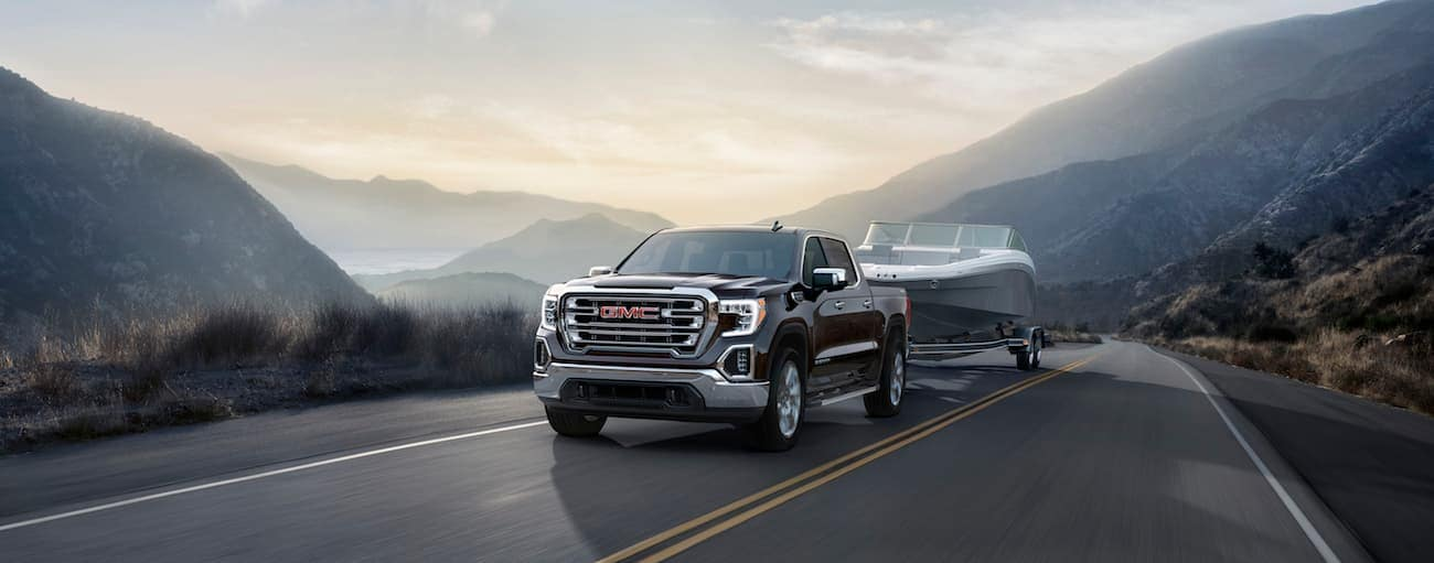 A brown 2019 GMC Sierra towing a boat on a mountain road