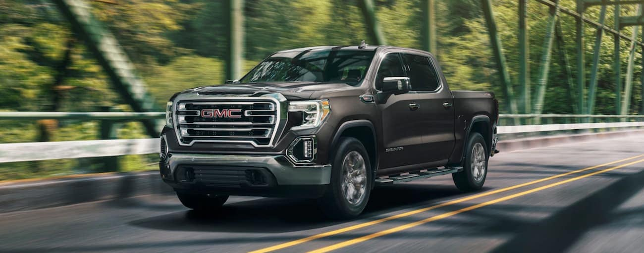 A brown/gray 2019 GMC Sierra driving over a woodland bridge